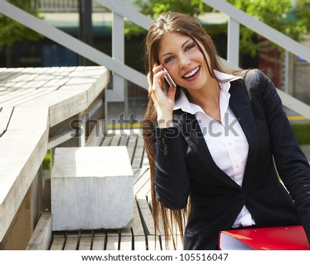 business woman with smart phone she is outdoors and holding red folder