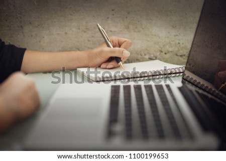 Business woman working at office with laptop and documents on his desk, Business woman holding pens and papers making notes in documents on the table, Hands of financial manager taking notes #1100199653