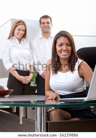 Business woman working on a laptop at the office and her team behind