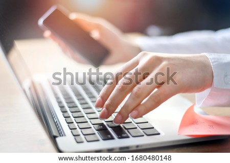 Business woman working on laptop computer on wooden desk as concept with social media success technology. Hands typing detail.