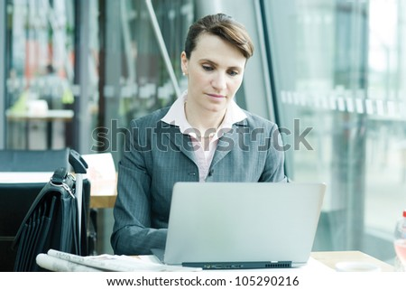 Business woman working on notebook at the airport lounge