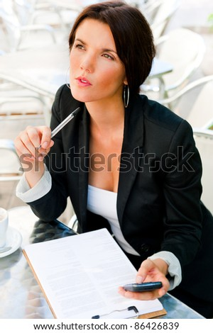 Business woman working with documents while having lunch or breakfast coffee at outdoor cafe near her office