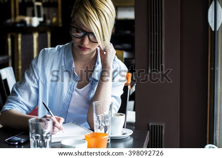 Business woman writing in a cafe