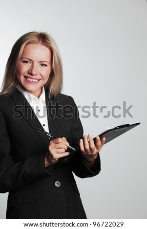 business woman writing in notebook on a gray background