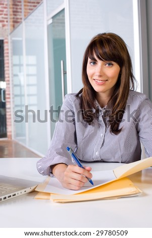 Business Woman Writing notes at desk in a modern office