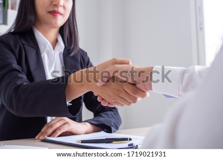 Business women and job seekers shake hands after agreeing to accept a job and approve it as an employee in the company. Or a joint venture agreement between the two businessmen