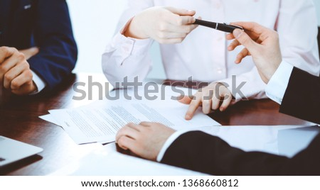 Business women giving a pen to businessman for contract signing. Agreement at negotiation or meeting. Success concept #1368660812
