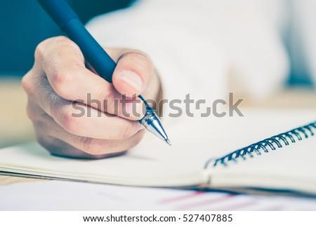 Business women hands working writing notebook on wooden desk, lighting effect