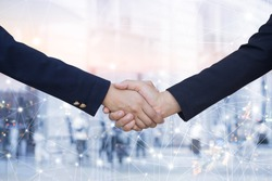 business women handshake agreement on blurred double exposure of city urban metropolis and connecting line technology effect background,ceo financial advisor hand shake together.