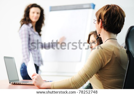 Business women holding a conference writing on an a board in an office