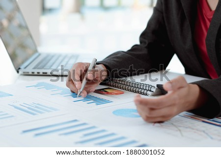 Business women sitting on a laptop and checking business graph documents, working in financial transactions, accounting Foto stock ©