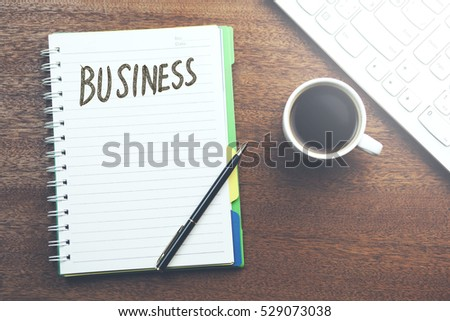 business word on notepad and  office supplies on table #529073038