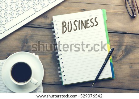 business word on notepad and  office supplies on table #529076542