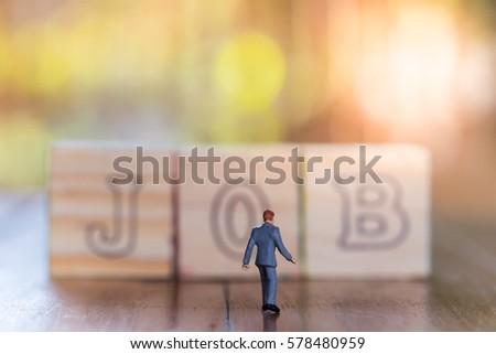 business work and target concept businessman miniature figure walking to j o b alphabet wooden blocks