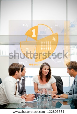 Business workers using yellow pie chart interface in a meeting