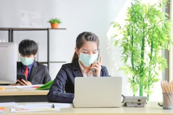 Business workers wearing medical face mask for social distancing in new normal situation for virus prevention in the office reopen and answering phone call from customer during the coronavirus disease
