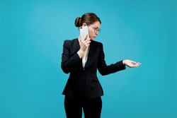Business young woman in a business suit speaks on the phone and holds out her hand to the side as if taking documents