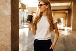 Business young woman in sunglasses walking in city with cell phone