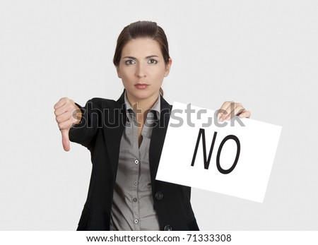 Business young woman showing thumbs down and holding a paper card with the word NO