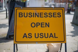businesses open as usual sign during coronavirus pandemic
