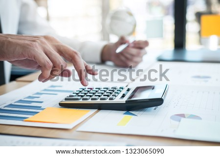 Businessman accountant working analyzing and calculating expense financial annual financial report balance sheet statement, doing finance making notes on report.