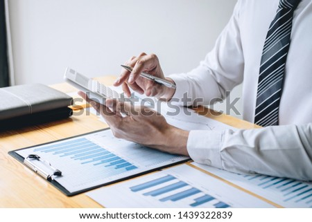 Businessman accountant working analyzing and calculating expense financial annual financial report balance sheet statement and analyze document graph and diagram, doing finance making notes on report.