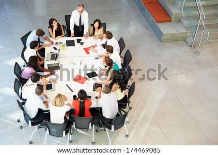 Businessman Addressing Meeting Around Boardroom Table stock photo