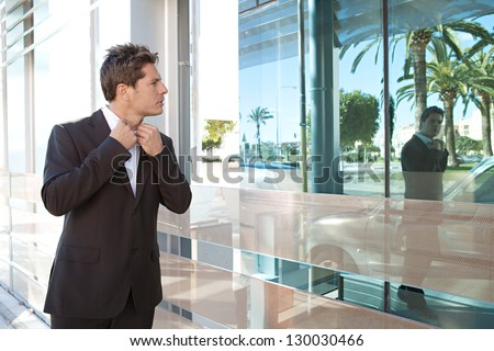 Businessman adjusting his shirt neck collar on a modern office building glass reflection as he walks through the financial city district.