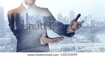 Businessman against modern city background . Mixed media #518724499