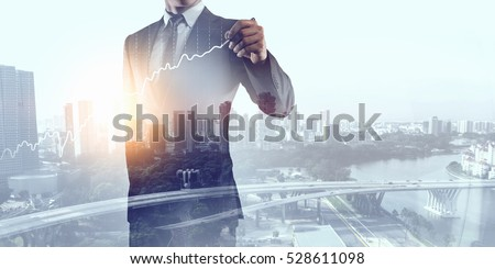 Businessman against modern city background . Mixed media #528611098