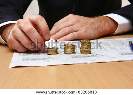 Businessman allocating  coins on the stock chart diagram