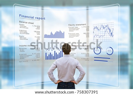 Businessman analyzing financial report data of the company operations (balance sheet, income statement) on virtual computer screen with business charts, fintech