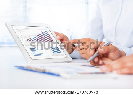 Businessman analyzing graph using digital tablet touch pad touching hand point finger touch screen business people group desk office businesspeople report financial charts