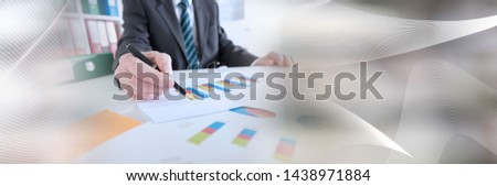 Businessman analyzing graphs at office; panoramic banner