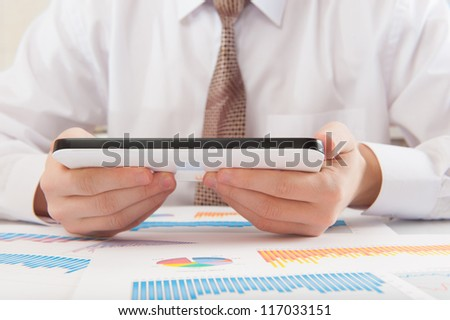 Businessman analyzing graphs using modern digital tablet device