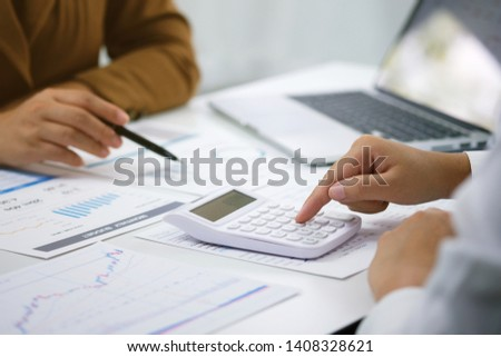 Businessman analyzing investment charts and pressing calculator buttons over documents. Accounting Concept #1408328621