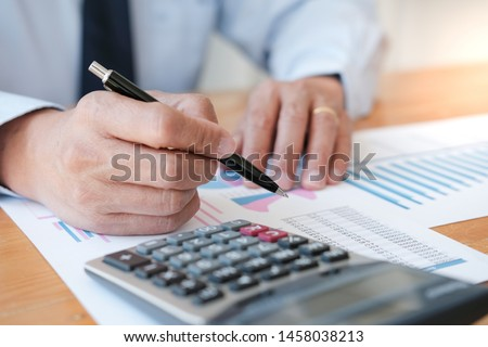 Businessman analyzing investment charts and pressing calculator buttons over documents. Accounting Concept