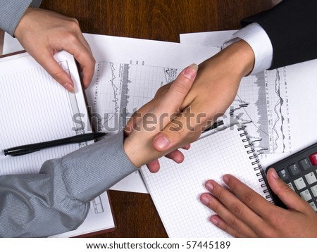 Businessman and business woman sign contract and shaking hands