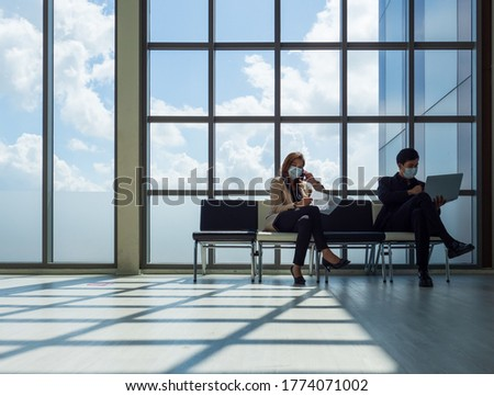 Businessman and business woman wearing protective mask sitting  giving distance between seats for protection during pandemic outbreak of Coronavirus, Covid-19.