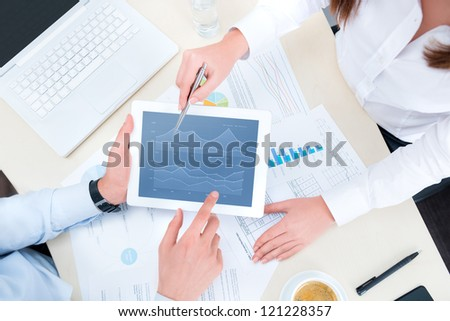 Businessman and businesswoman analyzing financial report on a modern digital tablet. Top view shot.