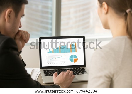 Businessman and businesswoman analyzing project statistics data on laptop screen, partners discussing infographic information about company growth, annual report analysis, close up rear view #699442504