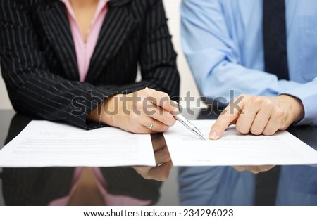 businessman and businesswoman are pointing to article of the treaty