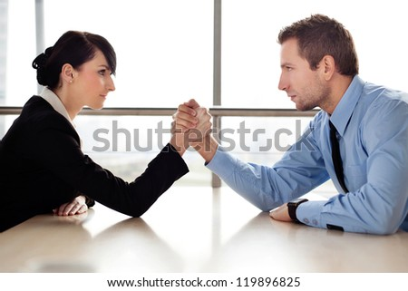 Businessman and businesswoman arm wrestling on desk in office