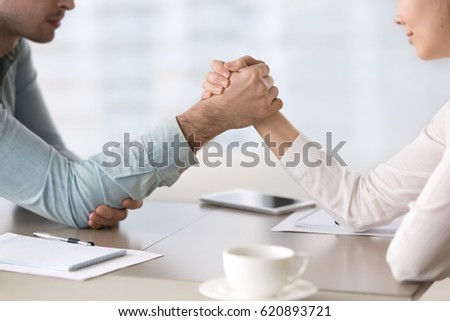 Businessman and businesswoman armwrestling at the office table, maintaining eye contact, trying to get leadership, fighting for equal rights for women, business competitors in the marketplace Photo stock ©