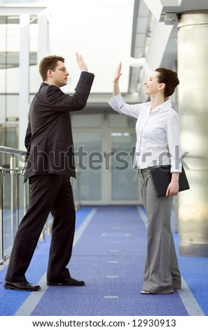 Businessman and businesswoman celebrating success by doing the high-five