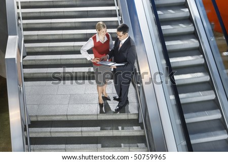 Businessman and businesswoman conversing on stairs, elevated view