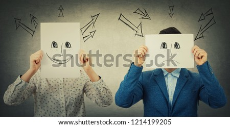 Businessman and businesswoman covering their faces using sheets with drawn happy and sad emoticons, like a mask to hide her real emotion from society. Fake identity concept. Introvert vs extrovert.