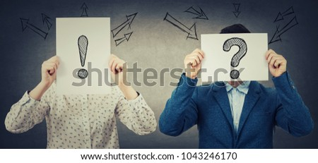 Businessman and businesswoman covering their faces using white paper sheets with drawn interrogation and exclamation marks, like a mask, for hiding identity. Introvert and extrovert.