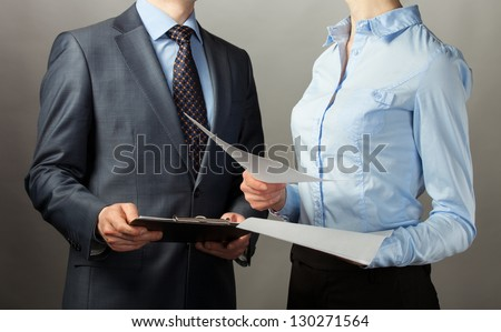 Businessman and businesswoman discuss a plan of work, grey background