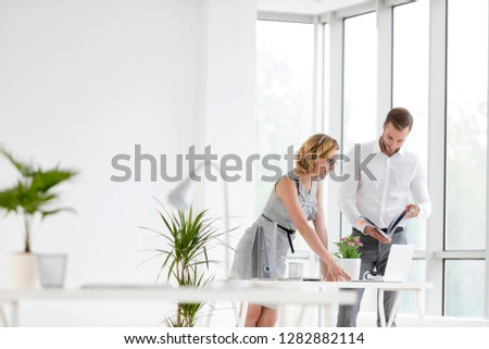 Businessman and businesswoman discussing at desk in new office #1282882114